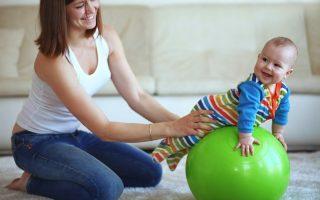 Mamá estimulando los sentidos de su bebé con una pelota verde de pilates