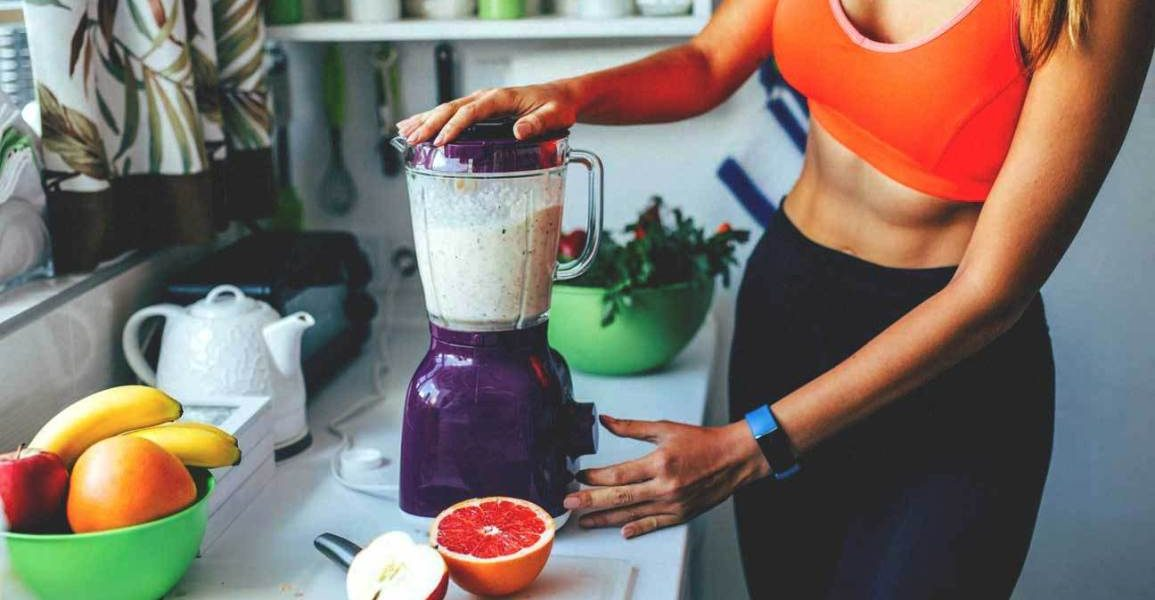 mujer haciendo un batido de proteínas